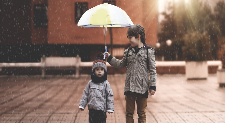 Brother holding umbrella for his younger brother ; image used for HSBC Philippines HSBC Safeguard