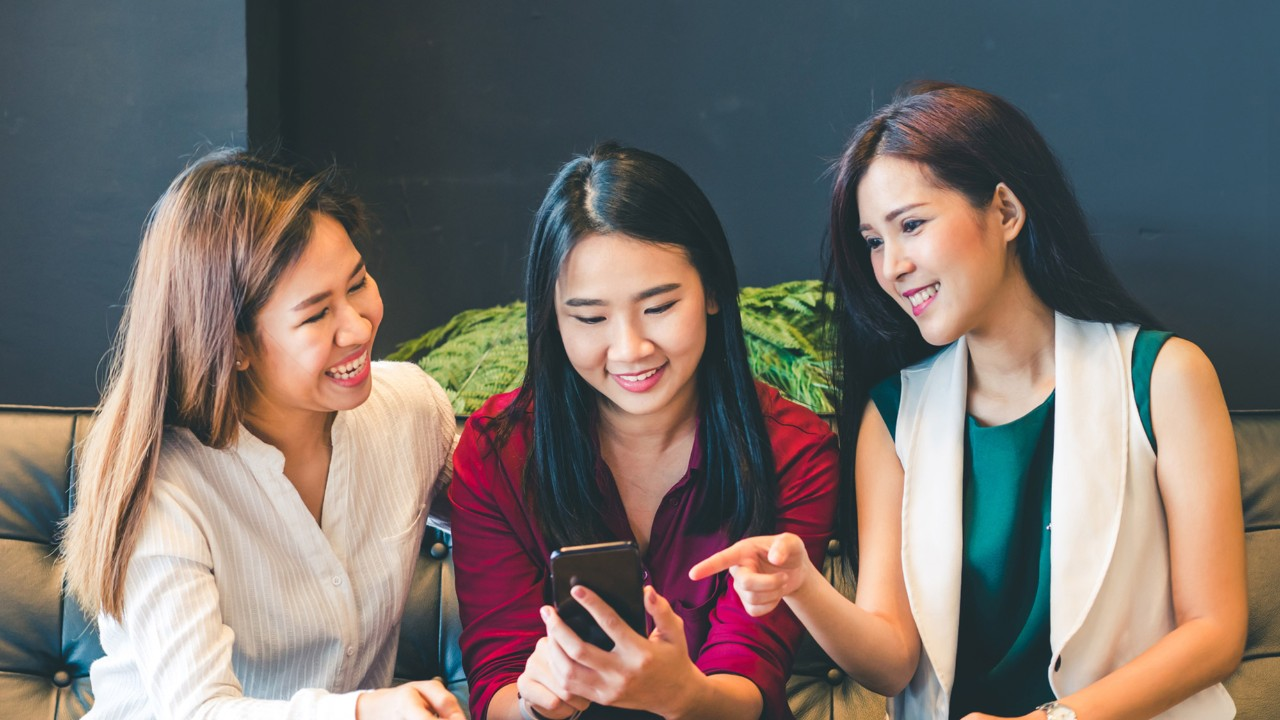Three female friends using a phone on couch; image used for HSBC Philippines Credit Cards Features Text Alert page