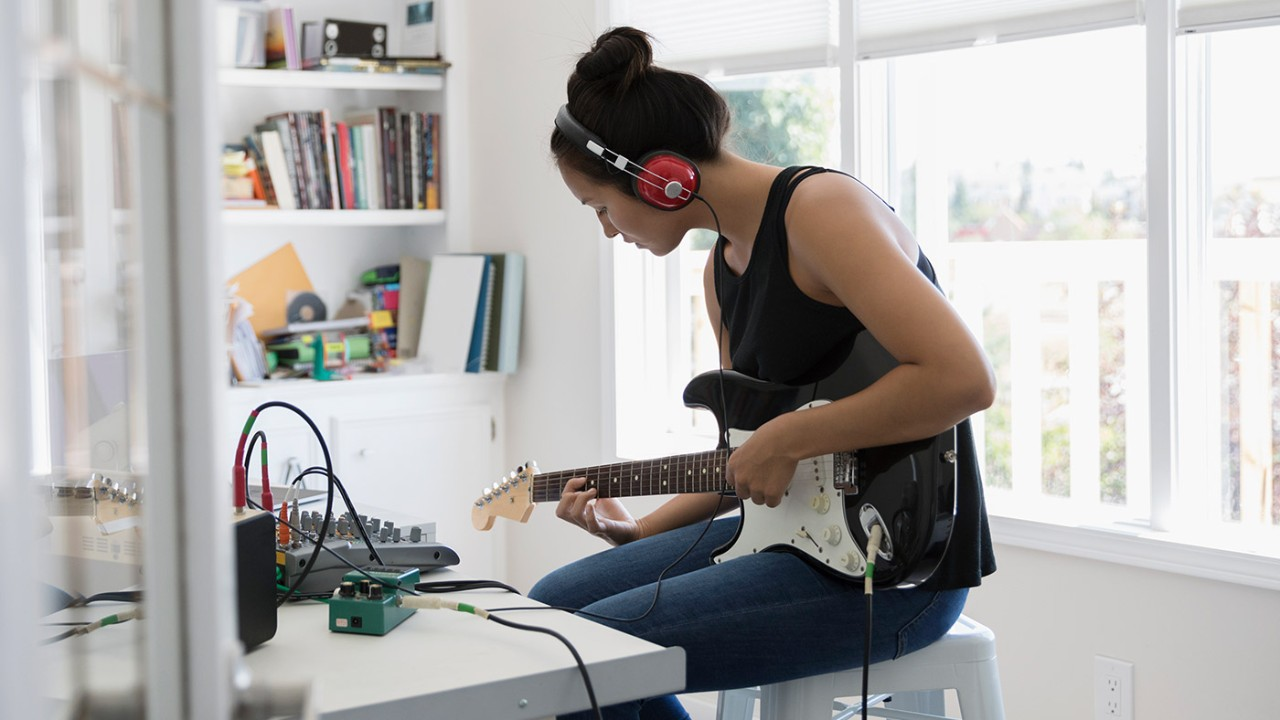 Woman listening to music and playing guitar; image used for HSBC Philippines Asset Link