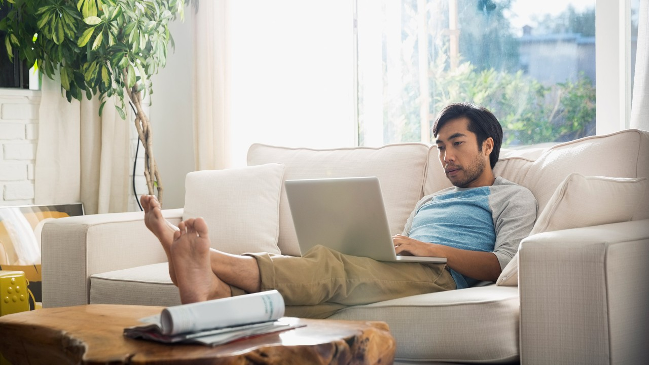 Beaded asian man using laptop at home; image used for HSBC Philippines Credit Cards Features eStatements page