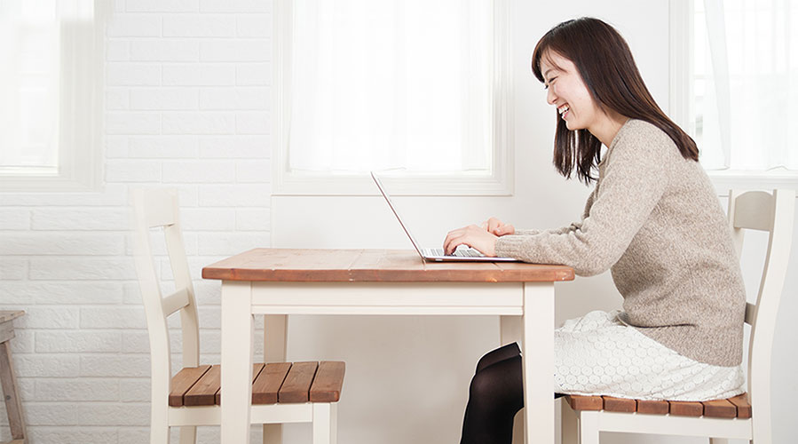 Woman sitting at dining table on computer; image used for HSBC Philippines What Can I Afford article page