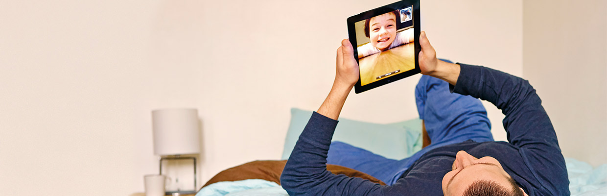 Father video calling his child on ipad; image used for HSBC Philippines Advance Online Tools page