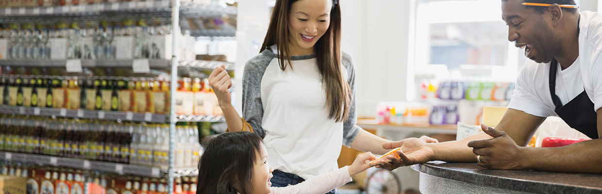 Mother and daughter at cashier counter in grocery store; image used for HSBC Philippines Credit Cards Features Contactless page