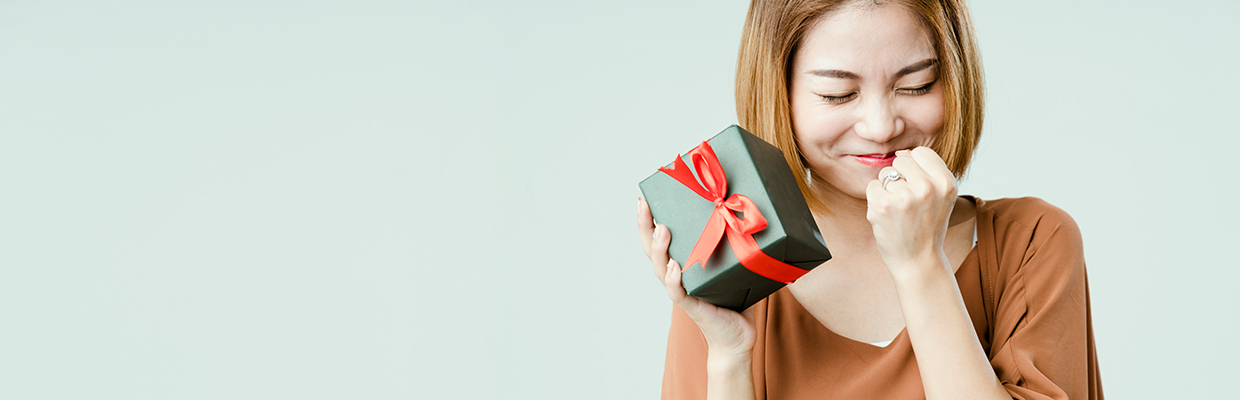 Woman excitedly holding a wrapped gift; image used for HSBC Philippines christmas 2020 promotion page