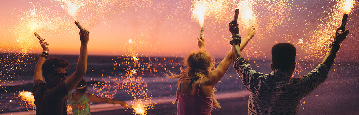 Four people play fireworks at beach, image used for HSBC credit card free annual fee campaign.