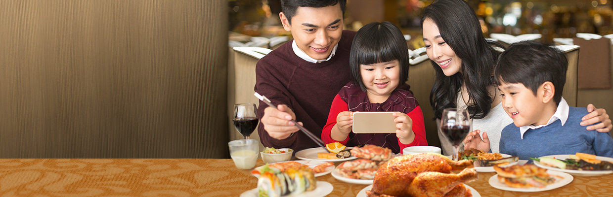 A family enjoys dinner with several foods; image used for HSBC Credit Cards Application Campaign