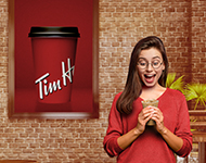 Women excitedly holding a Tim Hortons drink