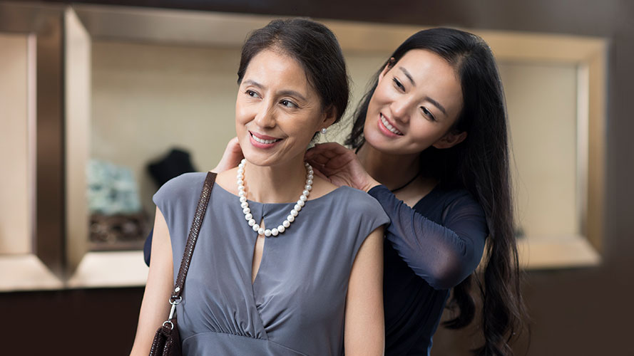 Daughter helping mother put on pearls; image used for HSBC Philippines Premier Offers Member Get Member page
